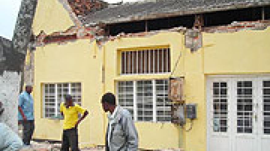 Residents gathered to closely look at the house whose roof curved in. (Photo: B. Mukombozi)