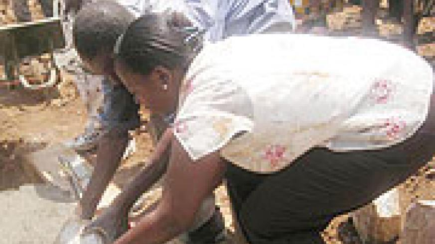 Minister Nsanzabaganwa lays a foundation stone at the launch of the classroom construction exercise in Mukura Sector.