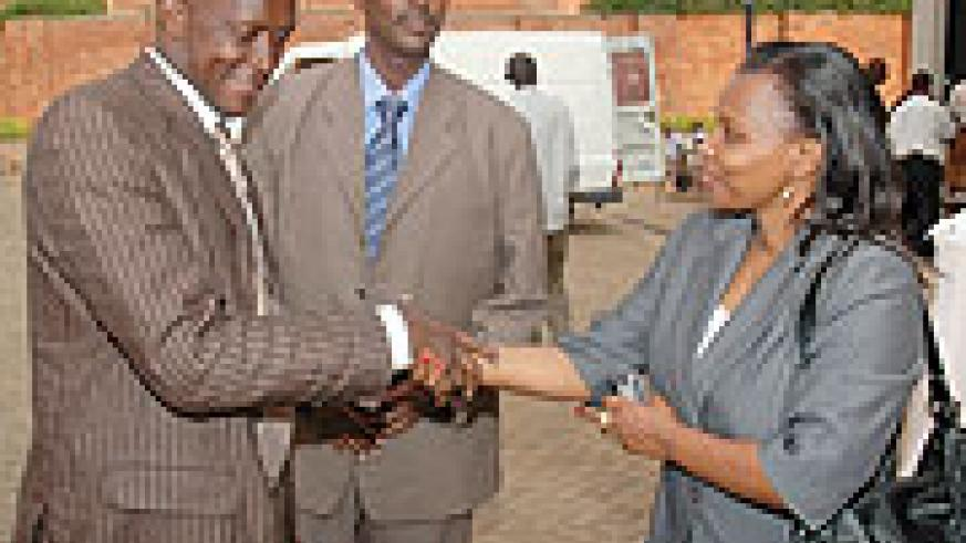 Minister Joseph Habineza (L) shakes hands with Christine Tuyisenge as the commission Executive Secretary Jean de Dieu Mucyo looks on. (Photo/ J. Mbanda)