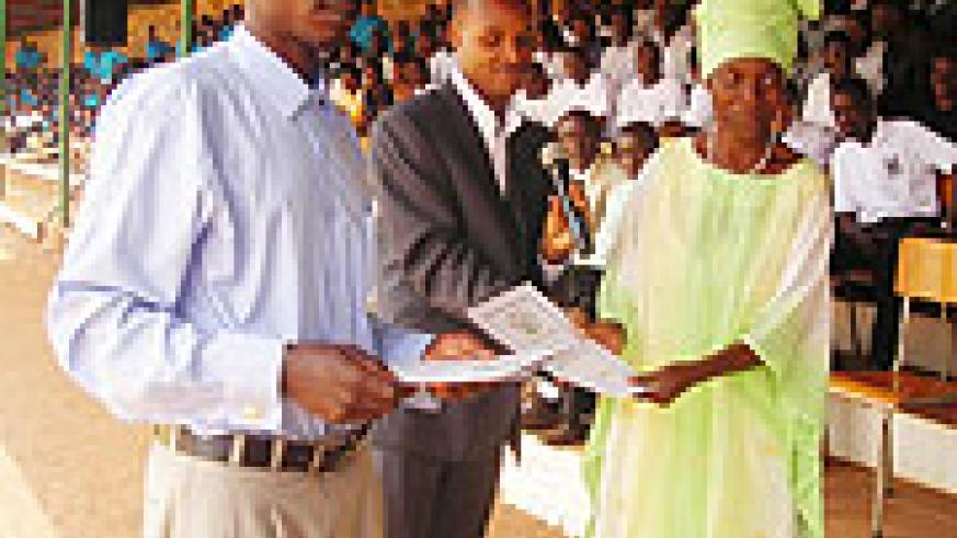 A Primary school teacher being awarded a certificate of merit in recognition of her dedication to work. (Photo/ P. Ntambara)