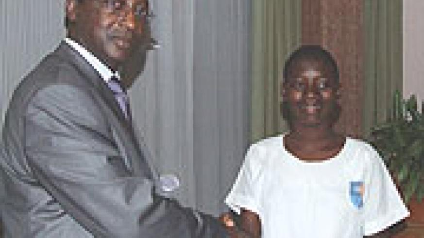 National Post Office Director General, Celestin Kayitare, congratulates Gentile Mahirwe after handing her a prize for best student writer of the year. (Photo/G.Mugoya)