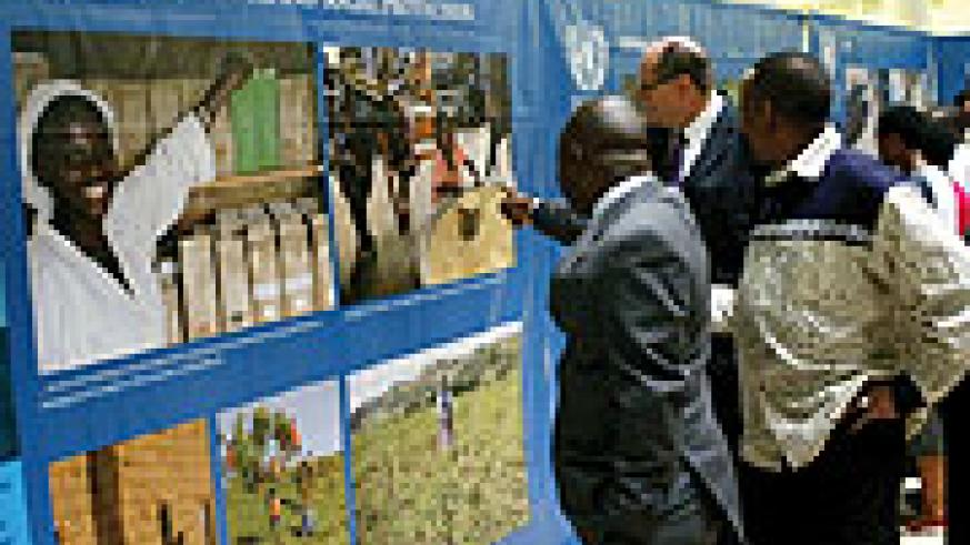 UN Resident coordinator Aurelien Agbenonci (L) and  other UN officials admire some photos at the exhibition. (Photo/ J Mbanda)