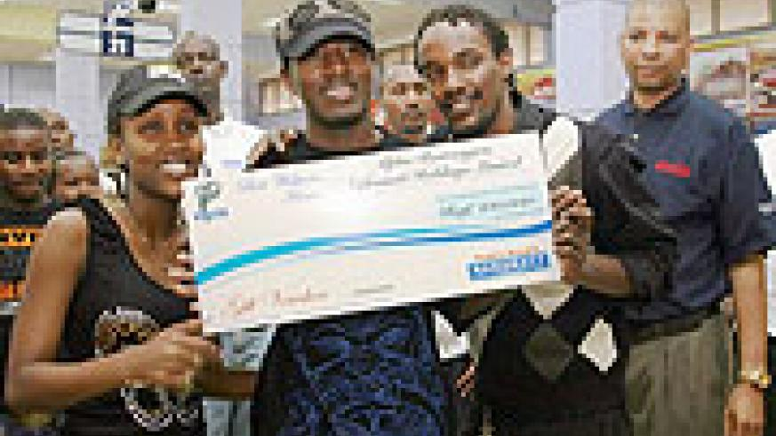 Alpha recieves a dummy cheque at the Nakumatt store in Kigali (Courtsey Photo)