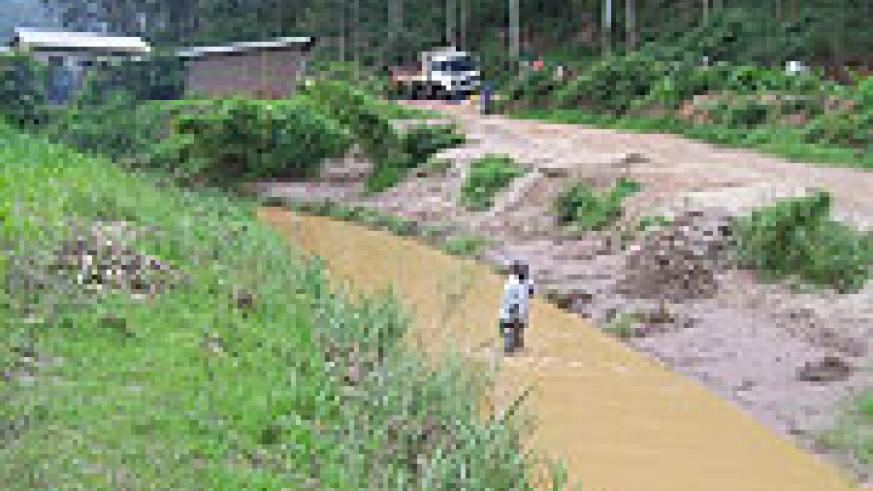 A man takes sand from River Rusine as a truck waits to load. Many residents abuse the river. (Photo /A Gahene)