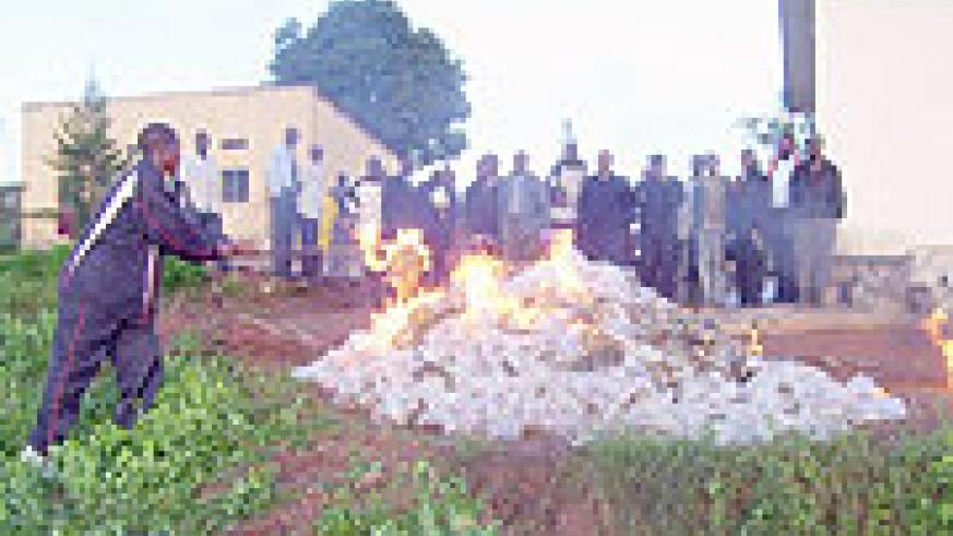 Local leaders and residents watch as banned  alcoholic drinks and marijuana goes up in flames at Byumba Police station on Monday. (Photo: A. Gahene)