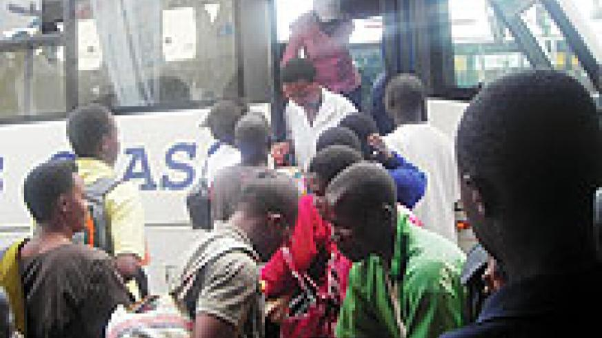 Students scramble to board one of the buses.