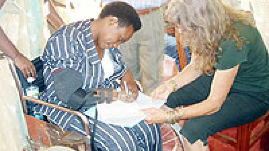 A lady learns how to write using a prosthetic hand, the beneficiaries from Rubavu will be able to perform such tasks with their newly acquired artificial  hands. (Photo: P. Ntambara)