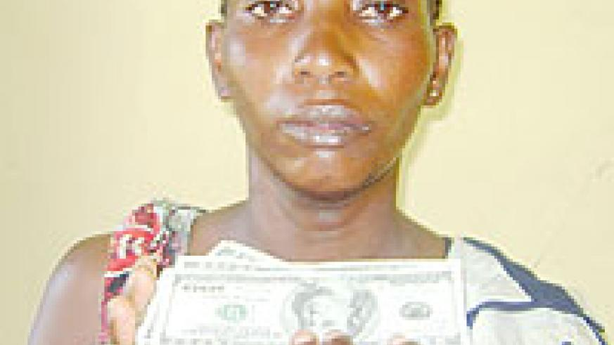ALONE AND FRIGHTENED; Anastasie Nyirankuriza with part of the money that was discovered from her parents' home. (Photo/ B. Asiimwe)