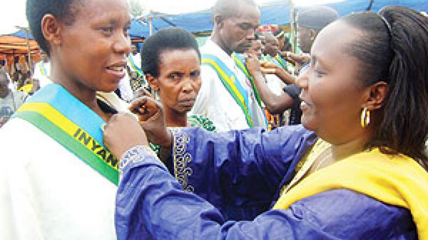 Domitile Mukantaganzwa decorates a judge with a medal. (Photo / S. Rwembeho)