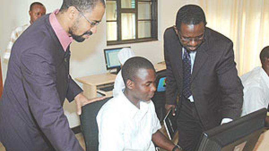 Al Bashir Project Manager Haitham B Yousif (L) and MINEDUC's Richard Niyonkuru inspect the donated computers yesterday. (Photo/ J. Mbanda)
