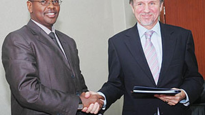 Minister of Finance James Musoni and Amb. Frans Makken shake hands after the signing. (Photo; J. Mbanda)