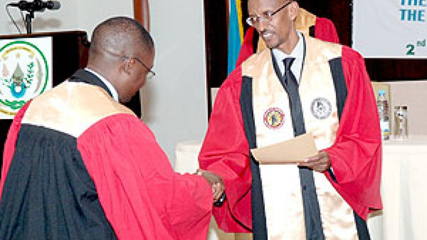 President Paul Kagame awarding one of the nine Surgeons that graduated during the COSECSA meeting yesterday. (Urugwiro Village photo)