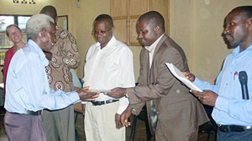 Dr. Emmanuel Nkurunziza hands over a certificate of attendance  to a local leader. (Photo: S. Rwembeho)