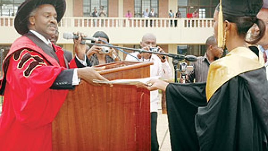 CONGLATULATIONS: Education Minister Charles Murigande hands the best student, Nibaruta Mahoro, a cetificate of excellence at the graduation ceremony yesterday (photo. F. Goodman)