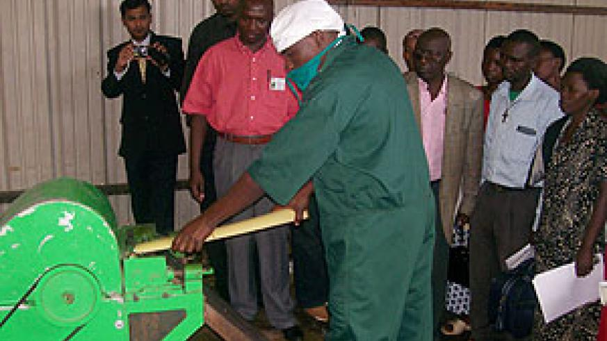 Trainees look on as a Utexrwa employee demonstrates how to use a machine to extract banana fibre. (Courtesy photo)