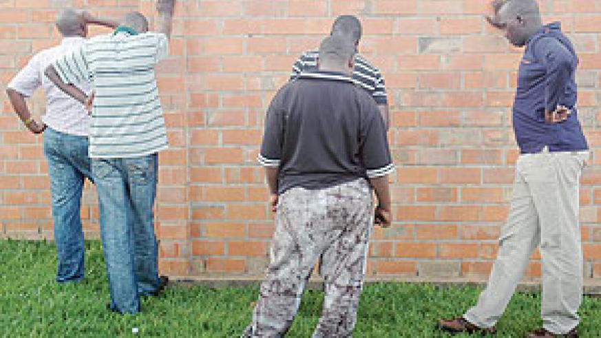 Some of the arrested loan sharks hiding their faces from the camera. ((Photo: F. Goodman))