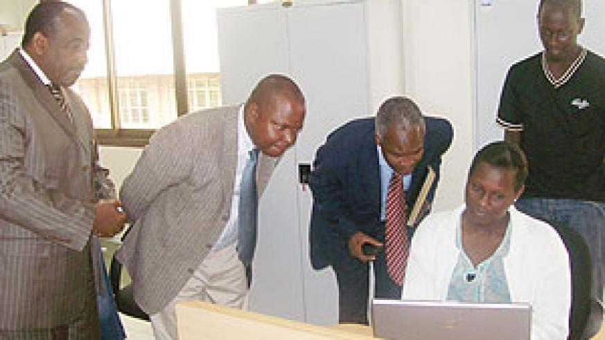 Education Minister Dr Charles Murigande and WDA Director General Dr Jean Damascene Gatabazi look on as Lucie Kabatesi takes them through the Rwanda LMIS website (courtesy Photo)