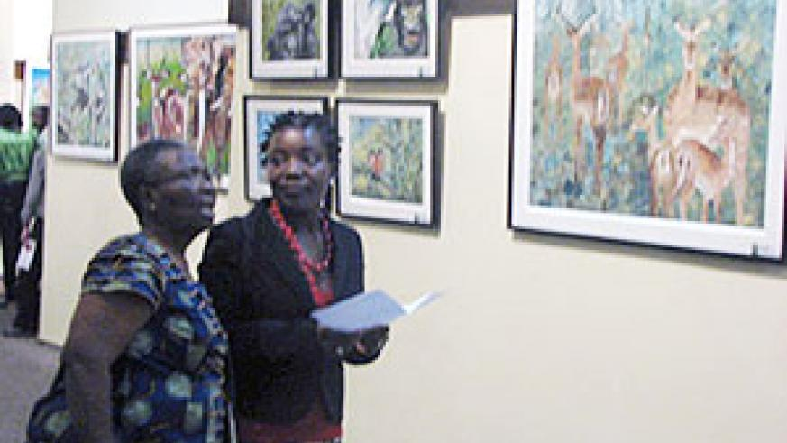 Sandra Idossou (wearing a red necklace), explains to one of the guest the paintings.