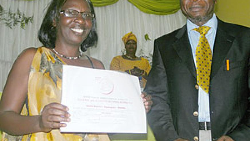 Odette Kayirere displays the award, on her right is the CAFOD representative. (Photo: S. Rwembeho)