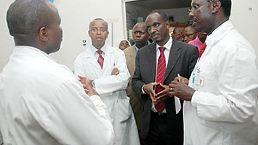 Health Minister Richard Sezibera with Kigali central Hospital Director Theobald Hategekimana and other staff during the Minister's tour of the Hospital Yesterday. (Photo J Mbanda)