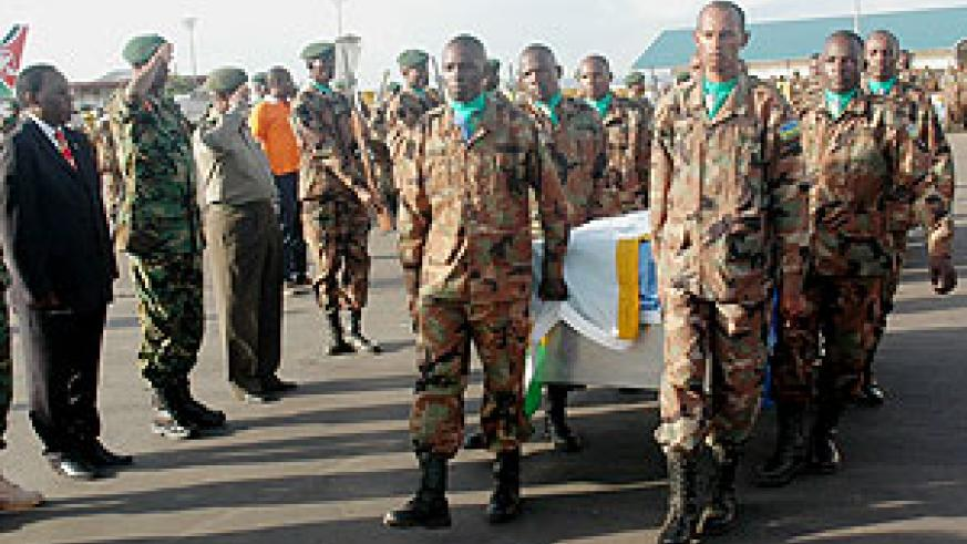 Soldiers carrying caskets bearing the remains of the fallen soldiers yesterday at Kigali International Airport (Photo John Mbnada)