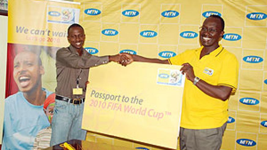 WINNER'S SMILE; Newtimes's Bonnie Mugabe receives the passport ticket to watch the 2010 World Cup from MTN's Chief Operations officer Andrew Rugege yesterday.