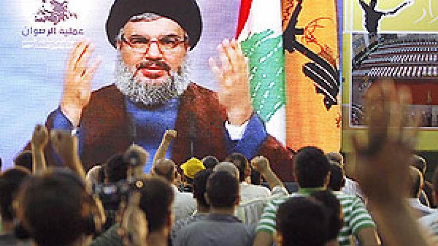 Lebanese Hizballah supporters listen to a televised speech by the party's chief Hassan Nasrallah during a celebration marking the first anniversary of the prisoners swap with Israel