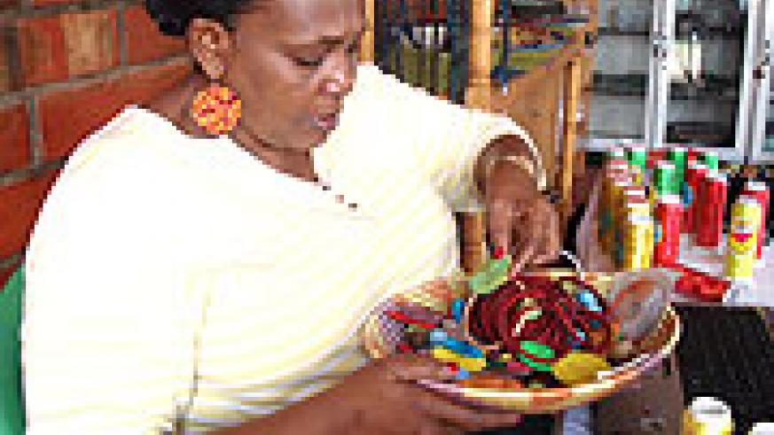 Joy Ndungutse, the Chief Executive Officer Gahaya Links sorts out earings that are ready for sale.
