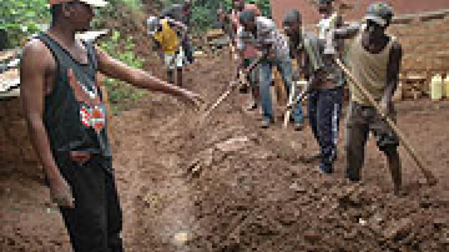 Residents of Rugarama village in Kinyinya sector of Gasabo District dig trenches yesterday to divert rain water from their houses. (Photo/ J. Mbanda)