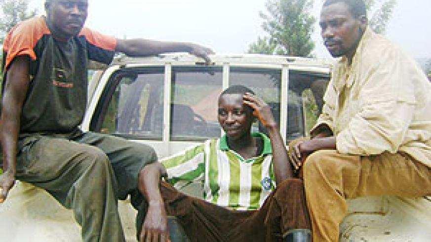 Eugene Habiyaremye (seated in middle) being driven to the police station following his arrest by community policing agents. (Photo: S. Rwembeho)