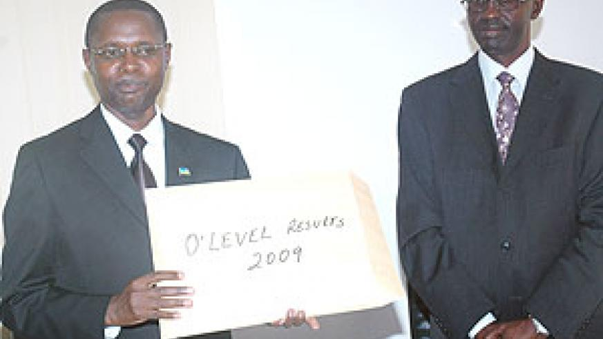 State Minister for Primary and Secondary Education, Mathias Harebamungu (L), displays 2009 O'Level results as RNEC's John Rutayisire looks on yesterday. (Photo/ J. Mbanda)