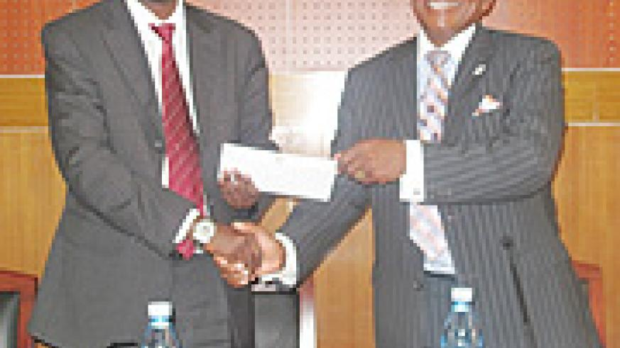 Dr Richard Sezibera receives the cheque from Ambassador Gladstone Dumisani Gwadiso.