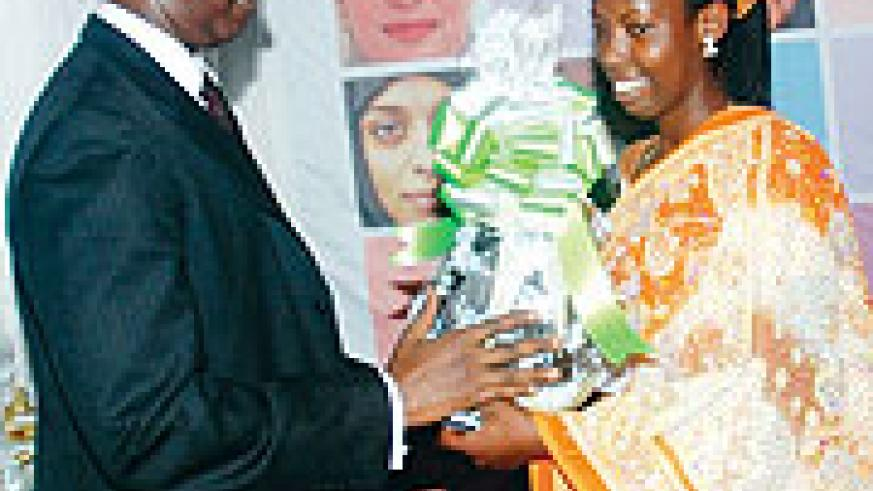 The first best performer Ernestine Musengerwa receives a gift from the Permanent secretary of the Ministry of Commerce and Industry Antoine Ruvebana. (Photo: J Mbanda)