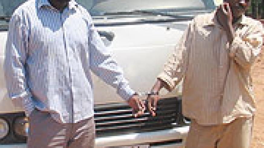 Gasamunyiga (L) and Ndumuhire (R) infront of the vehicle they allegedly stole. (Photo/ B. Asiimwe)