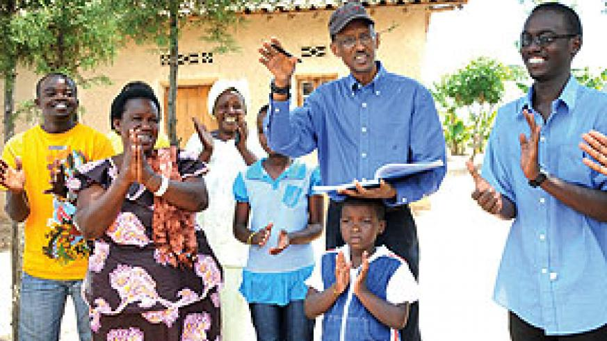 President Kagame signs an autograph for Alphonsine Mwubahimana and her family after visiting her dairy project