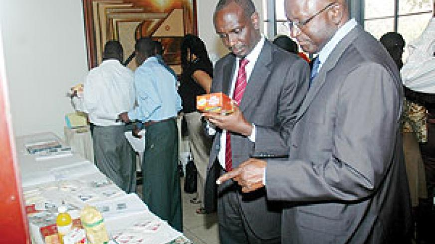 Health Minister Dr Richard Sezibera (L) and the U.S Agriculture attaché in Nairobi Diaby Souleymane examine Soybean flour on display at the conference. (Photo J Mbanda)