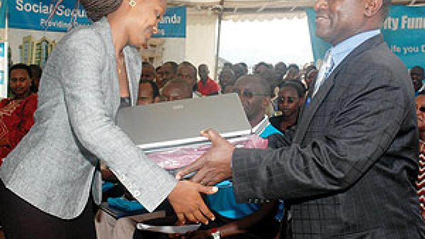 CSR   Director General Henry Gaperi hands a lap top to the overall winner of the CSR quiz Florance Mukashema. (Photo J Mbanda)