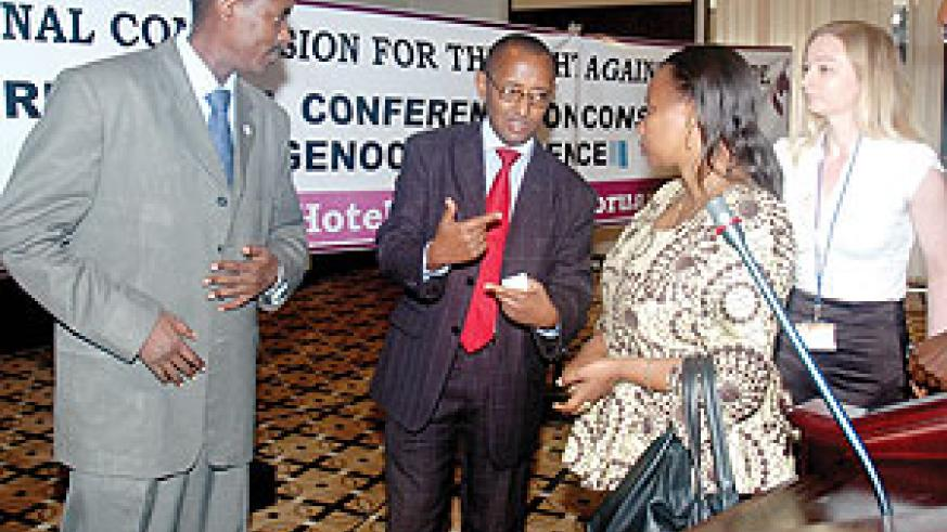CNLG Executive secretary Jean de Dieu Mucyo listens to his staff Deogene Bideri and Christine Tuyisenge, with Amanda Roberts a forensic expert (R) during a conference on preservation of Genocide evidence. (Photo J Mbanda)