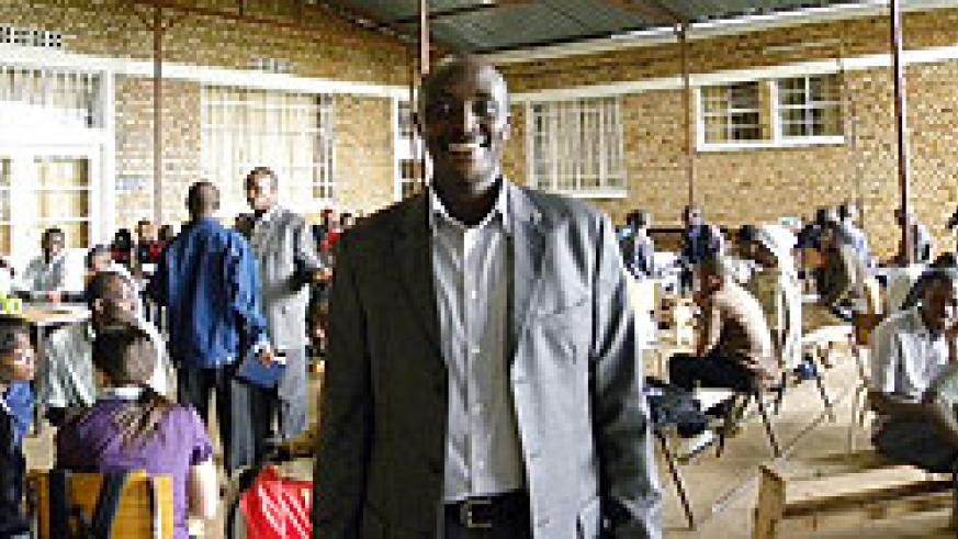 NUR Legal Aid Clinic Coordinator, Aimable Havugiyaremye, poses for the camera. In the background are clients and their students (Photo B.Kimenyi)