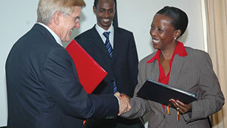 German Ambassador to Rwanda Elmar Timpe (L) and Rwandan Foreign Minister Louise Mushikiwabo shake hands after signing the agreements yesterday. (Photo J Mbanda)