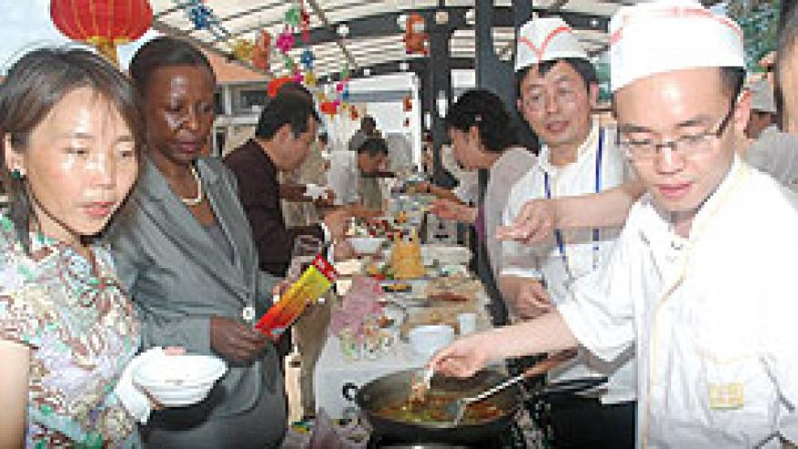 Foreign Affairs Minister Louise Mushikiwabo (2nd left) being shown some of the  food at the Chinese food Festival in Kigali Yesterday.(Photo J Mbanda)