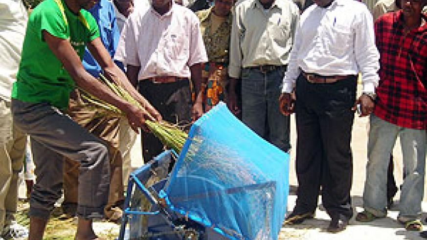 A local rice farmer demonstrating the use of  the newly introduced rice thresher.(Photo / P.  Ntambara)