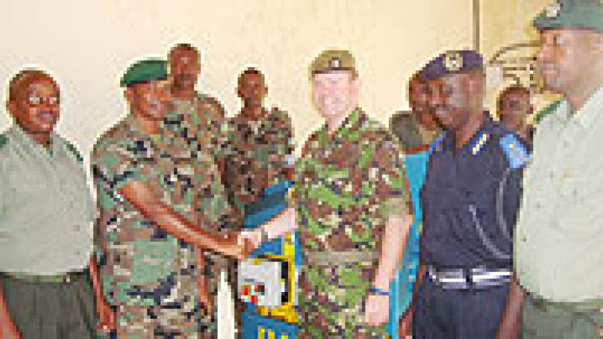 UK Defence Attaché, Lt. Col. Simon Etherington, officially hands over the equipment to Lt. Col. Innocent Kabandana, as other officers look on