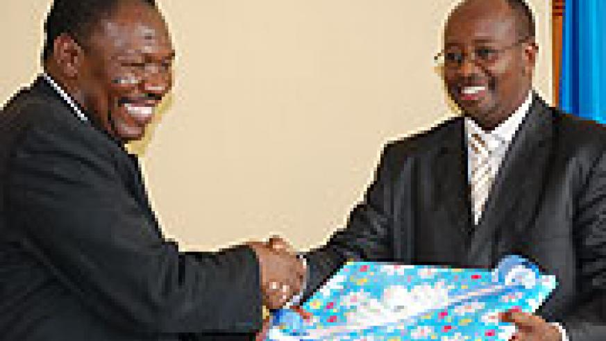 Agrey M. Mwanri, Tanzania's deputy minister in the PM's office exchanging a gift with Minister James Musoni yesterday (Photo J Mbanda)