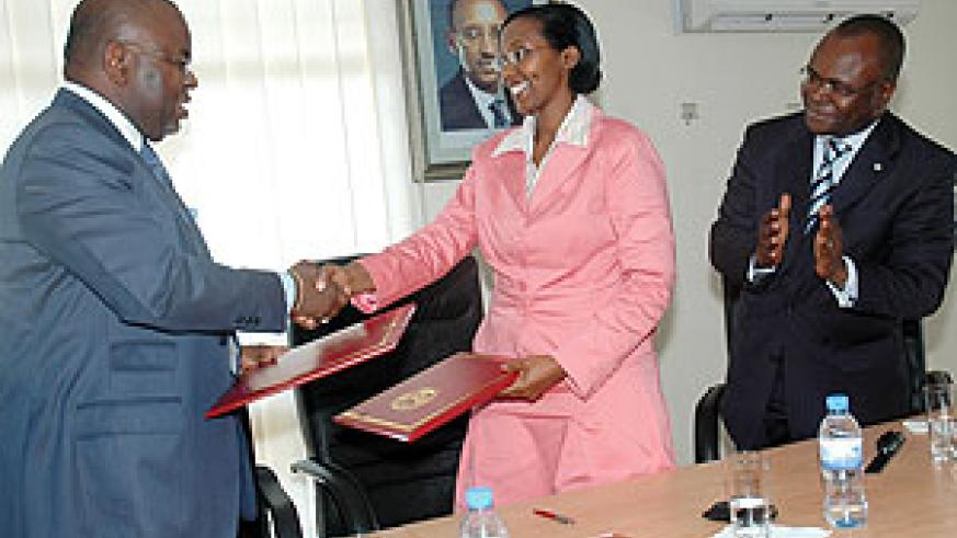 Congolese Minister of Energy and Water Resources, Bruno Jean-Richard Itoua, and Minister of State for Water and Energy Colette Ruhamya, shake hands after signing as Aurelien Agbenonci looks on (Photo J. Mbanda)