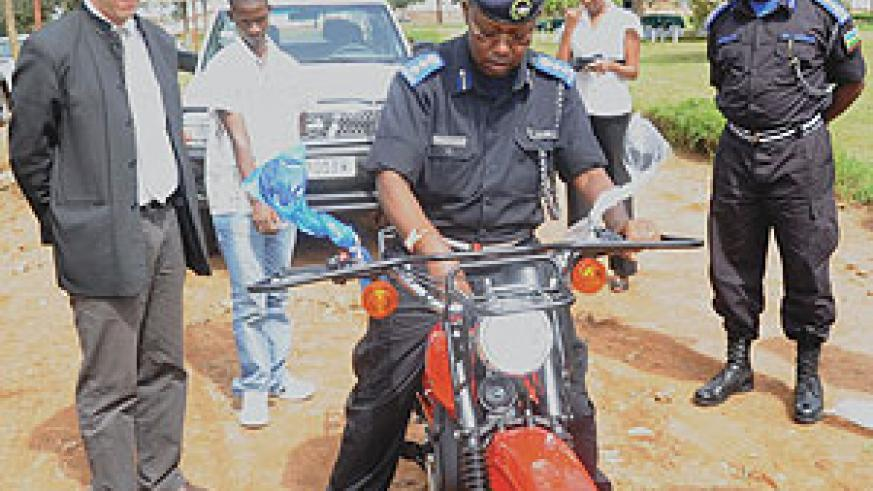 Chief Sup. Jimmy Hodari tests one of the motorcycles as Police Chief Emmanuel Gasana (R) and BTC's Jean Yves Saliez look on yesterday. (Photo/ J. Mbanda)