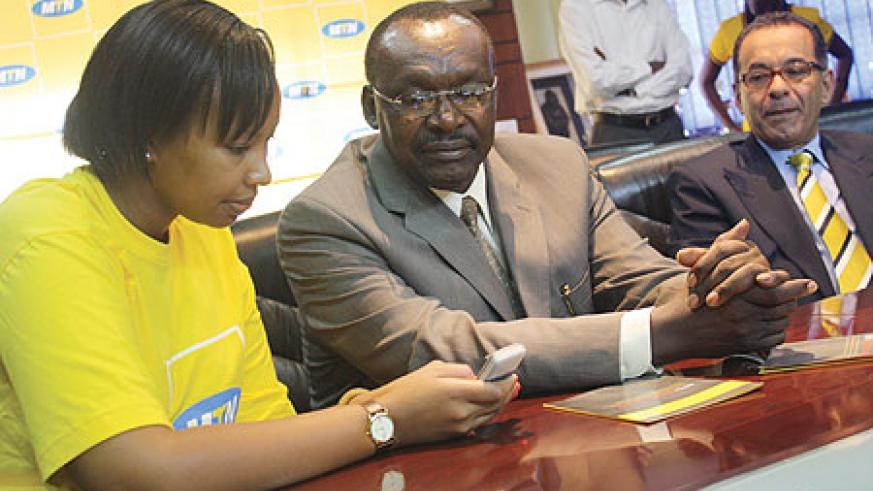 Governor Francios Kanimba recieves a demonstration recently, on how Mobile Money works. Looking on is MTN CEO Khaled Mikkawi (Photo/ D. K. Musoke)