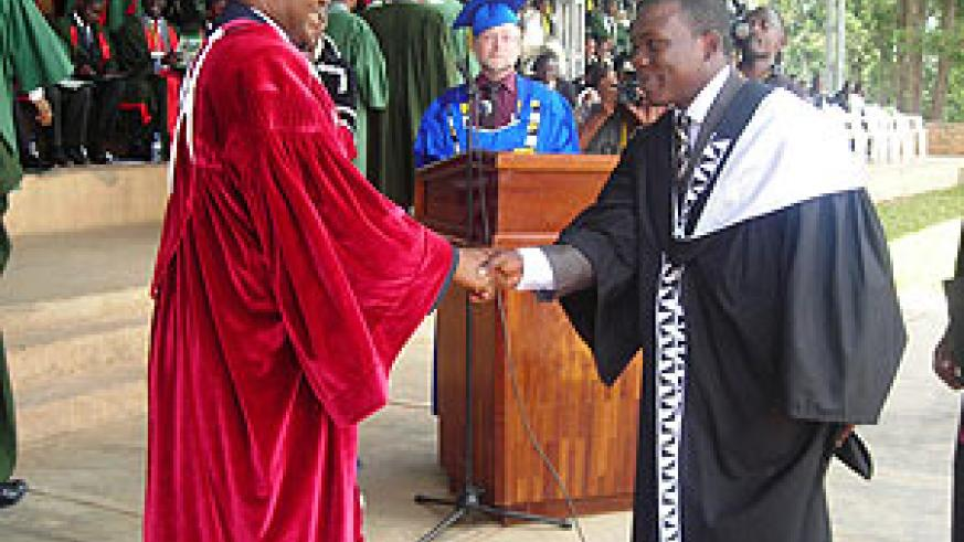 The Minister of Education, Dr. Charles Murigande congratulates one of the four students who attained a First Class degree at NUR yesterday. (Photo; P. Ntambara)