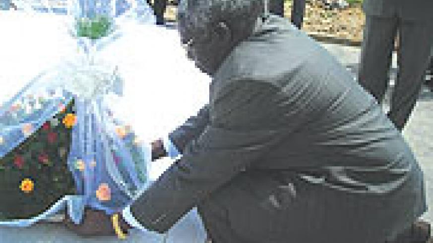 Dr.William Shija laying a wreath on grave at Murambi genocide memorial site in Nyamagabe district. (Photo/ J. Bucyensenge)
