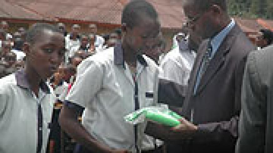 State for education, Dr. Mathias Harebamungu, hands over a laptop to one of the beneficiaries at SOS Primary School yesterday (Photo; F. Goodma